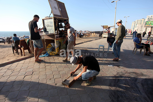 Moawia Ashour, 24, a Palestinian man uses coal to draw on a wooden board near his street cafe, at the beach of Gaza city, July 30, 2019. Photo by Mahmoud Ajjour