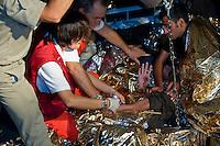 Lampedusa,2011. Volontari del Cisom, il Corpo di Soccorso dell'Ordine di Malta, impegnati nelle operazioni di salvataggio di immigrati.
