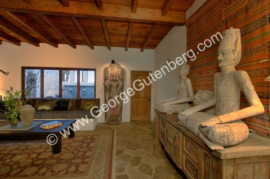 Small white walled living room with wood beamed tongue-in-groove ceiling,  South East Asian artifacts and decorating items