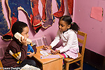 Education Preschool 3-4 year olds pretend play area boy and girl stting at desk  girl writing and boy holding stuffed animal toy and making telephone call horizontal