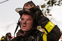 A Probie Firefighter from Engine 308 after operating at a two alarm fire in Ozone Park, Queens. The fire was in Sugman Fashion House on Monday, August, 21.