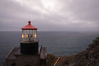 A view of the Pacific Ocean with Point Sur Light Station's light house in the foreground.  The sun has just set, and low marine clouds cover the sky, while the light can be seen rotating.  The view from the lighthouse is just stunning; this image includes more of the hillside than #1.