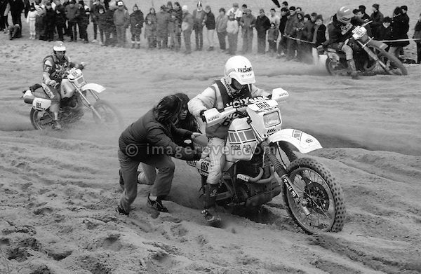 Enduro du Touquet 1987. Yamaha 600 Tenere. Dirt bike beach race at Le Touquet, Normandy, France. --- No releases available, but releases may not be necessary for certain uses. Automotive trademarks are the property of the trademark holder, authorization may be needed for some uses. --- Info: A thousand motorcycles take part in this mad event. The race starts along the beach, followed by a run into the sand dunes. The entry point in the dunes is most spectacular: All motorbikes have to pass through a small opening in the dunes. Once the fast professional drivers have flown through, this first passage developes into a true bottleneck with many hundreds of motorbikers trying to get through at the same time. Motorcycles are strewn all over the place. Many have fallen, others have already broken down. In the meantime, the professional riders are progressing quickly. But their riding style changes from racing full-out as soon as they are approaching the lappers from behind. Outmaneuvering them at high speeds is an art form! After three hours it's all over.....