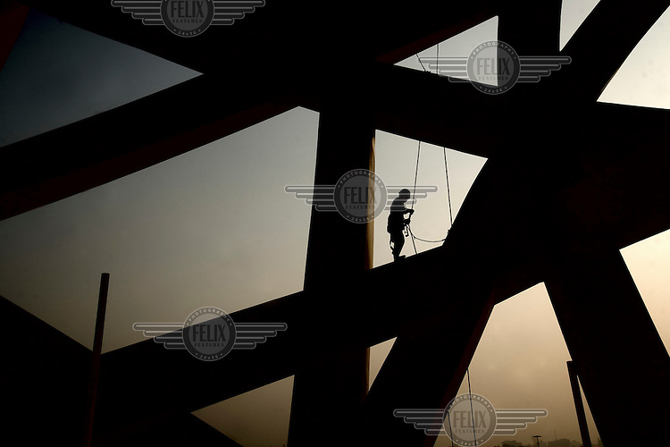 """A construction worker builds the """"Bird's Nest"""" National Stadium, which will be unveiled for the 2008 Olympic Games."""