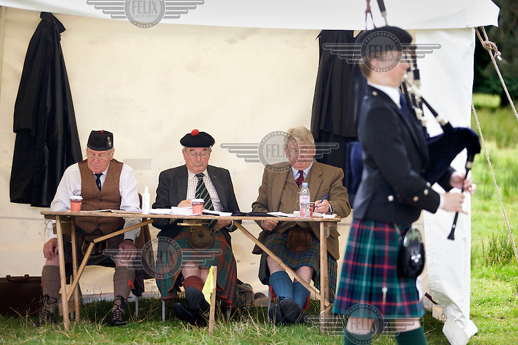 Judges listen to a piper competing in the bagpipe finals at the Inveraray Highland Games, held at Inveraray Castle in Argyll.