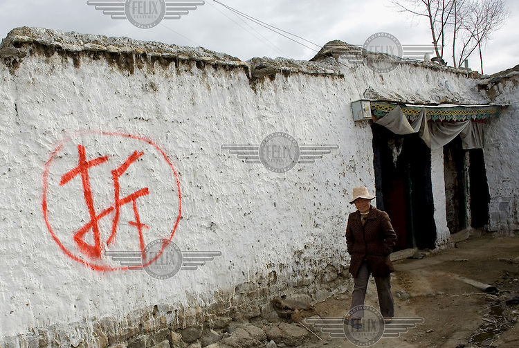 A woman walks past a traditional house with the Chinese word 'chai', which means 'demolish', painted on its exterior. The homes in the area are scheduled to be knocked down and the occupants will be moved to more modern dwellings.