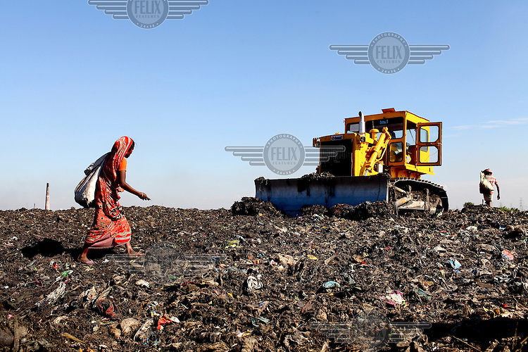 A young woman passes a bulldozer as she looks for recyclable material at the biggest rubbish dump in Dhaka. The city alone generates about 3500 to 4000 metric tons of solid waste each day.