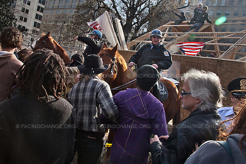 Washington, D.C.<br /> December 4, 2011<br /> <br /> U.S. Park Police push back crowds with horses as they set up a perimeter around the newly constructed building and the protesters within it.<br /> <br /> Summary: Occupy D.C.'s overnight construction of a large wooden structure in McPherson Square ended two months of relatively peaceful coexistence with the U.S. Park Police, who said that the building appeared to be a permanent structure and was therefore illegal. Occupy D.C. said that they were building it to protect themselves from increasingly cold weather. Protesters defied repeated orders to abandon the building and take it down -- setting the stage for a day long standoff -- which ended in 31 arrests and the destruction of the building by the Park Police.