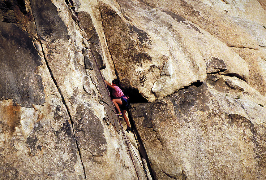 Woman rock climbing, Joshua Tree National Monument, California
