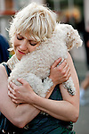 A young woman hugs a poodle in San Francisco, California, USA