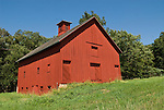 Red wooden barn with cupola ventilator along the highway in Nebraska.