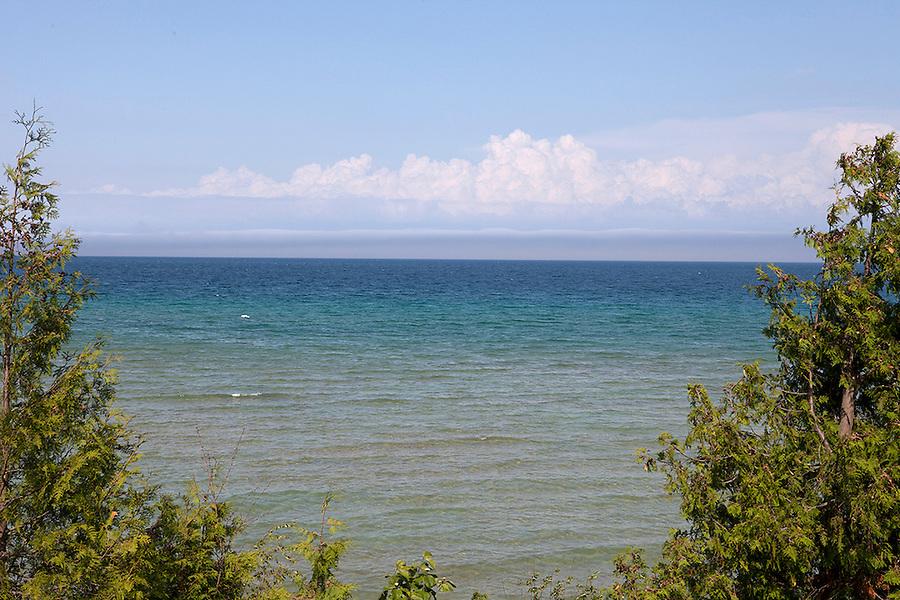 View through trees of Lake Michigan on beautiful summer day from Old Mission Peninsula, Lake Michigan, Traverse City area, Michigan, USA