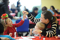 STAFF PHOTO ANDY SHUPE - Kimberly Covington of Fayetteville, right, sits with her 4-year-old daughter, Emmy, left, and 2-year-old son, Malachi, as they make Christmas tree drawings during an artsy-craftsy event Friday, Dec. 19, 2014, at the Fayetteville Public Library.