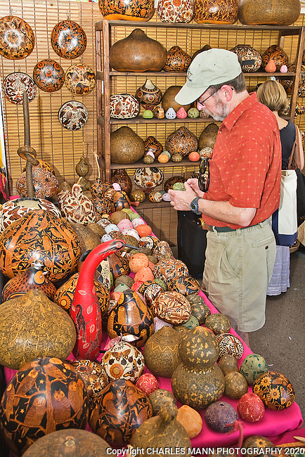 The Santa Fe International Folk Art Market attracts a huge crowd of shoppers and features a wide variety of folk artists from all over the world.  A visitor examines intricate carved gourds made by Bertha Medina Aquino of Peru.
