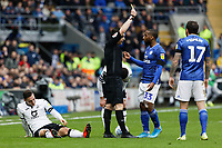 Referee Tony Harrington shows a yellow card to Junior Hoilett of Cardiff City for his foul against Connor Roberts of Swansea City (L) during the Sky Bet Championship match between Cardiff City and Swansea City at the Cardiff City Stadium, Cardiff, Wales, UK. Sunday 12 January 2020