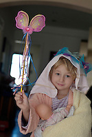 Little girl playing dress-up with a magic wand and baby doll.