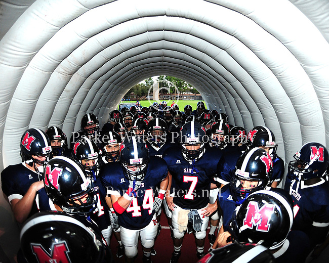 Members of the St. Martin's football team wait to run out of the tunnel for the start of their game against Crescent City. St. Martin's went on to win by a score of 40-0.