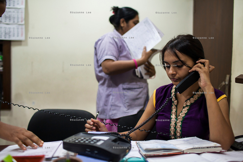 Dr. Nayana Patel's assistant, Dr. Hiral (right), tends to a phone calls in tandem with Dr Nayana Patel in the Akanksha IVF and surrogacy center in Anand, Gujarat, India on 10th December 2012. Surrogacy clients pour into Anand from across the world pursuing Dr Patel's expertise on the process, and they keep in touch with her and the progress of the pregnancies via the internet and phone. While 15% of couples are infertile globally, only 6% of infertility cases require surrogacy as a last option. Photo by Suzanne Lee / Marie-Claire France
