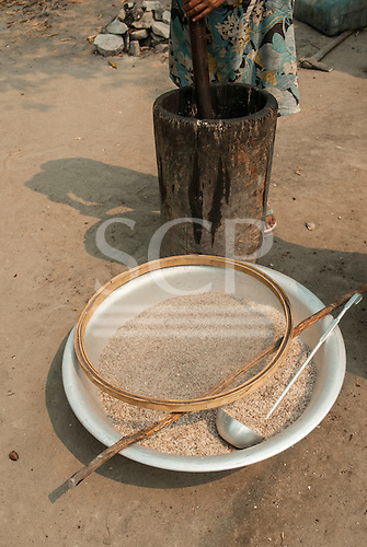 Aldeia Baú, Para State, Brazil. Aluminium bowl of crushed babassu nuts with sieve and ladle; woman crushing nuts in a pestle behind.