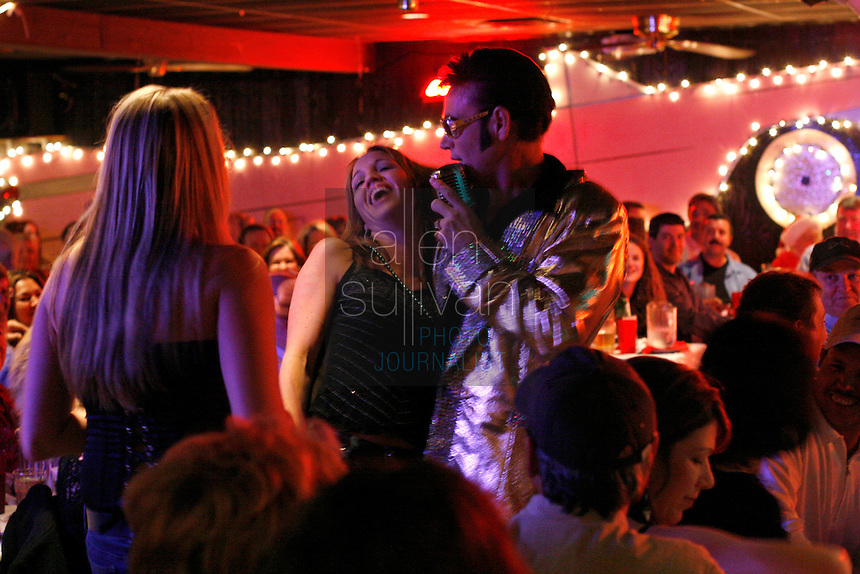 Mike Jones, as Elvis Presley, croons &quot;Blue Christmas&quot; to Liz Lehan (center), Melina Harris (left) and the crowd at The Lantern Inn, his family's restaurant in Gainesville, Ga., on Saturday, Dec. 16, 2006. Jones, who is 46 and a cook, has been performing as Elvis at the eatery for 18 years, but Saturday was the curtain call. The Lantern Inn closed its doors on Sunday after over 40 years of business.<br />