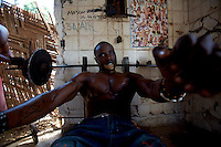 Nimley, 26 years old, finishes a series of chest press while lifting weights in his neighborhood improvised gym in Monrovia, Liberia on Tuesday  March 20 2007. .Marshall, Nimley and the other men working out are all unemployed. they spend their days at the gym to fight chronic depression..