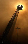 One of two ladder trucks is silhouetted against the sky after a fire in the Albertson's Shopping Center on Date Palm Drive and Gerald Ford Drive in Cathedral City, destroyed at least five business, Friday July 1, 2005. Albertson's not damaged and one fireman was reported with heat exhaustion.