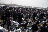 Uighur men look at motorcycles and scooters for sale at a used car market outside Kashgar, Xinjiang, China.