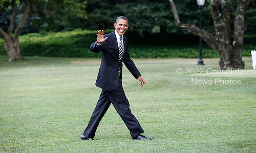 United States President Barack Obama waves to the photographers as he walks across the South Lawn of the White House in Washington, D.C. after a trip to Iowa on July 10, 2012..Credit: Dennis Brack / Pool via CNP