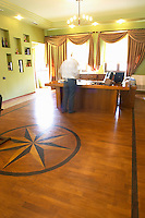 The office of the manager. with wood parquet floor with wood inlays in star shape. The general manager opening bottles to taste. Kantina e Pijeve Gjergj Kastrioti Skenderbeu Skanderbeg winery, Durres. Albania, Balkan, Europe.