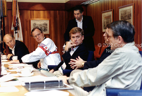 "Camp David, Maryland - August 4, 1990 -- United States President George H.W. Bush meets with national security advisors at Camp David to discuss Iraq on August 4, 1990.  From left ate Secretary of Defense Richard B. ""Dick"" Cheney; President Bush;  Vice President Dan Quayle; Defense Undersecretary Paul D. Wolfowitz (standing); White house Chief of Staff John Sununu; and Central Intelligence Agency (CIA) Director William H. Webster..Credit: White House via CNP"