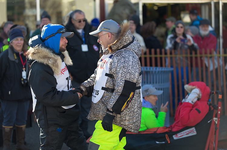 Mushers Jeff King and Jason Mackey greet each other at the ceremenial start of the 43rd Annual Iditarod in Anchorage, Alaska. Behind them, King's Iditarider gets instructions from a volunteer.