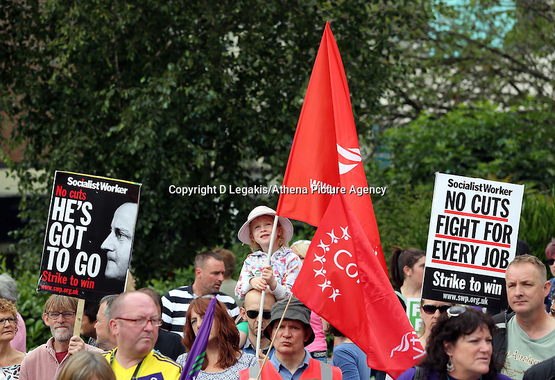 """Swansea, UK. Thursday 10 July 2014<br /> Pictured: A young girl holding a Unite Union flag among two Socialist Workers placards one reading """"No Cuts Fight for Every Job""""  and the other one showing Prime Minister David Cameron and reading """"He'sGot To Go"""" at Castle Square Gardens, Swansea, south Wales.<br /> Re: Strikes are taking place across the UK in a series of disputes with the government over pay, pensions and cuts, with more than a million public sector workers expected to join the action.<br /> Firefighters, librarians and council staff are among those taking part from several trade unions, with rallies taking place across the UK."""