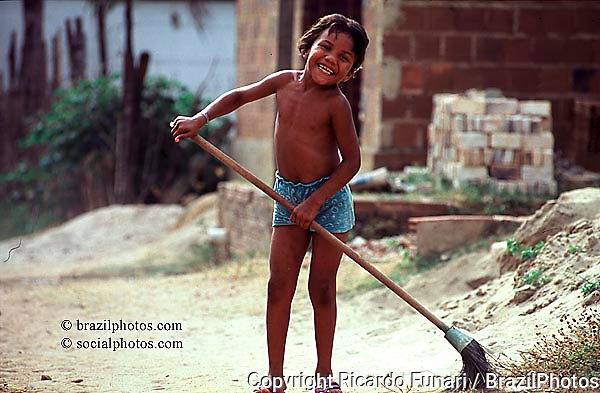 Latin America, Brazil. Dark-skinned girl holding a broom, sweeping the land street in front of her house in a poor neighborhood.