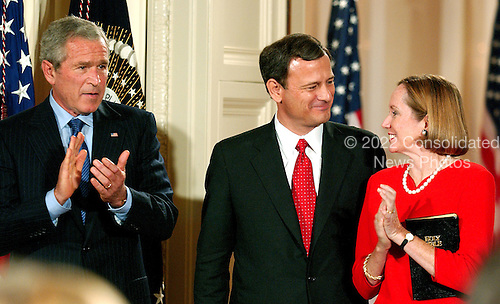 Washington, DC - September 29, 2005 -- John Glover Roberts, Jr., center, looks towards his wife, Jane Sullivan Roberts, right after he was sworn-in as the 17th Chief Justice of the United States by Associate Justice John Paul Stevens in the East Room of the White House in Washington, D.C. on September 29, 2005.  United States President George W. Bush looks on from left..Credit: Ron Sachs / CNP