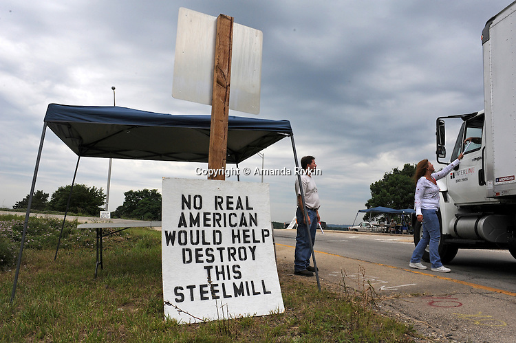 Denetta Reddick, 38, hands out a flyer to a passing trucker as Richard Erwin, 37, looks on as part of the informational picket outside the main gate of the Arcelor Mittal plant, which closed after several rounds of layoffs in between March 1-20, 2009, in Hennepin, Illinois on July 20, 2009.  The plant, owned by the largest steel company in the world, Mittal, and previously employed 280 hourly workers and an unknown salaried employees; an informational picket set up at both the main and west gates to the plant has claimed one major success, the refusal of a company to strip the plant and send the machinery offshore; both Erwin and Reddick worked at the plant for 7.5 months.