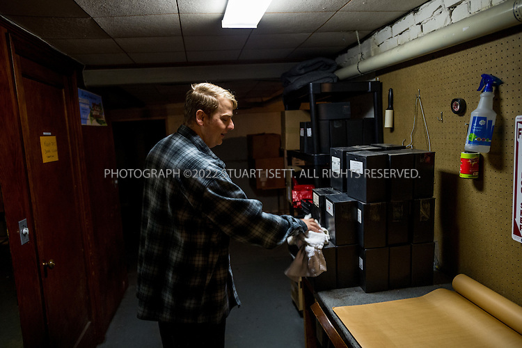 9/30/2016 -- Seattle, WA, USA<br /> <br /> <br /> Here: Undertaker James Lindley in the basement of the Columbia Funeral Home, gently dusts nearly two dozen urns containing the ashes of possible veterans, delivered to the funeral home by the King County Medical Examiner&rsquo;s office. Mr. Lindley is investigating each person to see if they can obtain a military funeral at the nearby Tahoma National Cemetery.<br /> <br /> James Lindley, 34, an undertaker and US Marine Corp Veteran, works at the Columbia Funeral Home in Seattle, Washington and has taken it upon himself to process the remains of indigent veterans and ensure their remains are placed in Tahoma National Cemetery in nearby Kent, WASH. The veterans are given full military funerals with active service members as well as volunteers who stand-in for unavailable next-of-kin, accepting the folded flags provided by the Veterans Administration.<br /> <br /> On this day, with the help of Mr. Lindley, the remains of 4 veterans were interred at the Tahoma National Cemetery: <br /> <br /> Richard Fesler, born 1951, died2014. US Army Veteran<br /> Rocky Stallone, born 1951, died 2014. Marine Corps veteran<br /> Russell Ristow, born 1944, died 2014. US Army veteran.<br /> Wayne Roberts, Born 1937, died 2014. US Navy veteran.<br /> <br /> <br /> Credit: Stuart Isett for The Wall Street Journal. <br /> VETBODIES<br /> <br /> &copy;2016 Stuart Isett. All rights reserved.