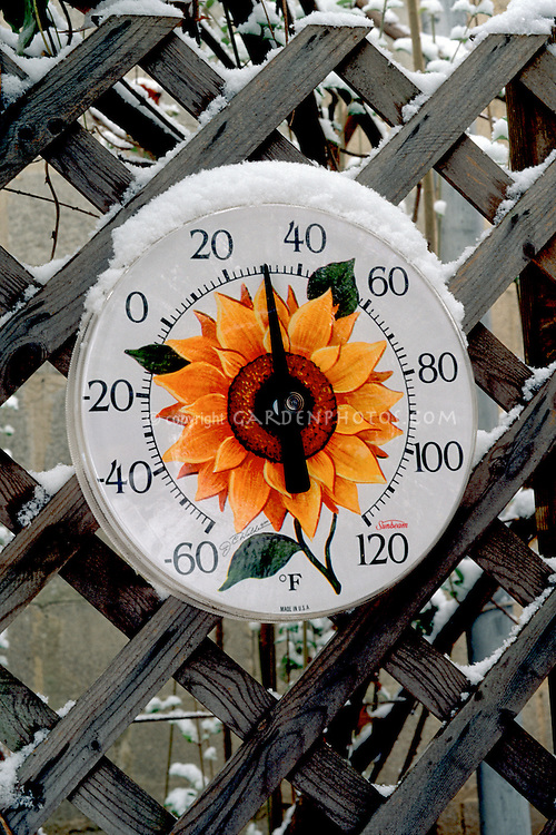 Freezing temperatures with garden thermometer and snow in winter outside