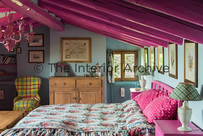 The beams of this pretty attic bedroom have been lacquered a bright pink, a colour echoed in the paintwork of the headboard and bedside tables