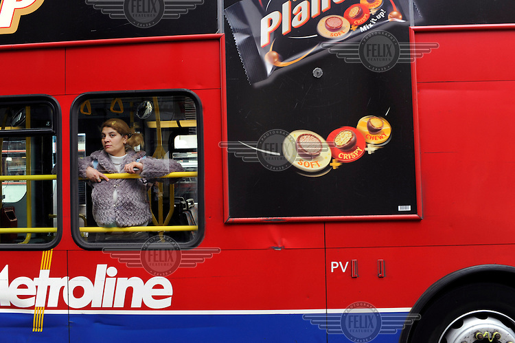 A woman watches from a London bus as thousands of protestors descended on the City of London ahead of the G20 summit of world leaders to express anger at the economic crisis, which many blame on the excesses of capitalism.