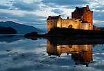A reflection in water at night, the famous, picturesque Eilean Donan Castle home of the MacRaes and Mackenzies, is at Lochalsh Scotland.  It is Scotland's most photographed castle, an icon of Scotland