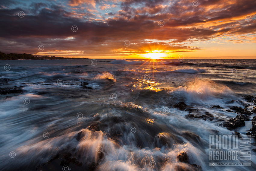 The rays of a brilliant sunset spill through clouds and over waves rushing to shore at Puako Bay, Big Island.