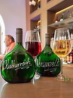 Germany, Bavaria, Lower Franconia, Volkach am Main: Franconian wine in Bocksbeutel bottles in wine bistro 'Mainwein' | Deutschland, Bayern, Unterfranken, Volkach am Main: Frankenwein in Bocksbeutel Flaschen im Weinbistro in Volkach
