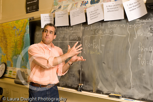 Education High School male math teacher calculus lesson including blackboard talking and gesturing as he explains concept t the class horizontal