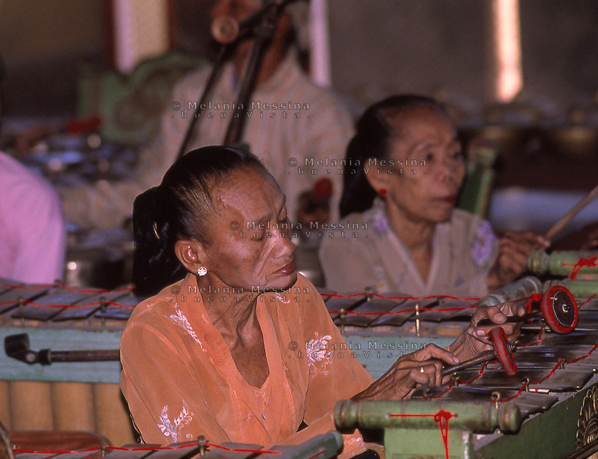 traditional gamelan orchestra musician playing during wayang kulit performance.<br />