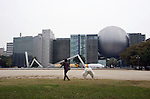 A woman walks her dogs through the park behind the city science museum in Nagoya, Aichi Prefecture, Japan on 13 Oct. 2011. Photograph: Robert Gilhooly