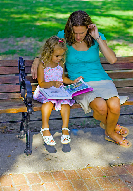 Mother and daughter reading in the park.
