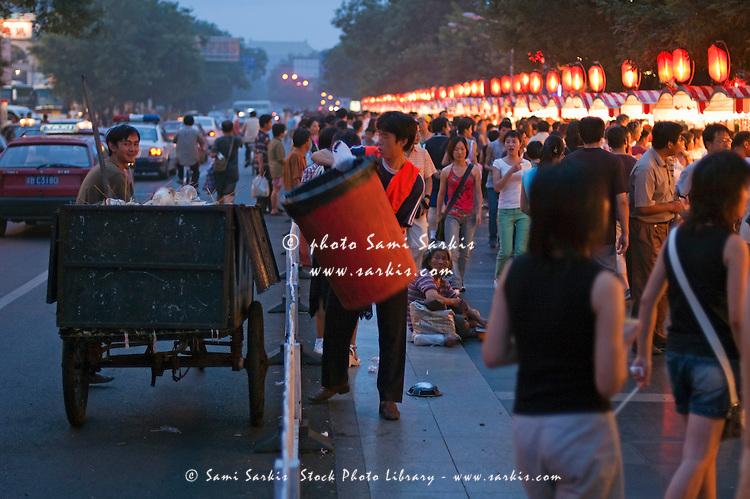 Men collecting rubbish at the Wangfujing night markets, Beijing, China.
