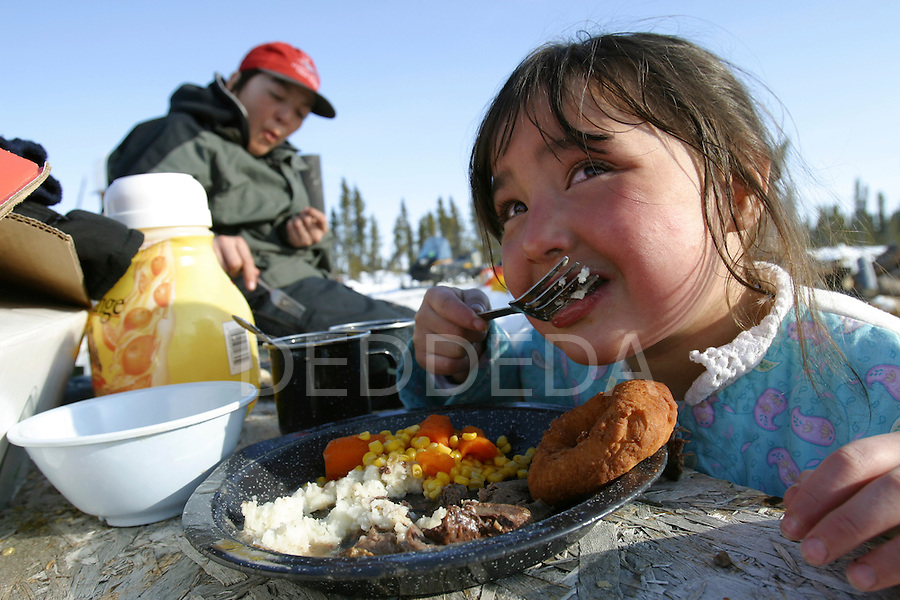 A young member of the Vuntut Gwitchin First Nation, Cheyanne Kapuchuk, 5, enjoys a meal of caribou meat at a traditional-style winter camp near Old Crow, Yukon Territory, Canada.