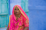 Rajasthani woman in traditional clothes sitting in front of house in Blue City (old town); the blue houses were originally for Brahmins but non-Brahmins soon joined in, as the colour was said to deflect the heat and keep mosquitoes away, Jodphur, Rajasthan, India --- Model Released