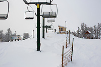 A lift operator clears snow from the Payload triple chair at Showdown Ski Area on King's Hill in the Little Belt Mountains near Neihart, Montana, USA.